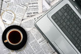 Workplace with laptop and coffee cup on newspaper background — Stock Photo
