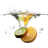 Fruits dropped in water with splash on white — Stock Photo