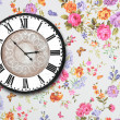 图库照片: Wooden retro clock on floral wallpaper