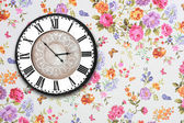 Wooden retro clock on floral wallpaper — Stok fotoğraf