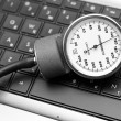 Sphygmomanometer on laptop keyboard — Photo #18403575