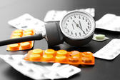 Blood pressure meter and pills on the table — Foto Stock