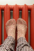 Feet with wool socks warming on the radiator — Stockfoto