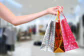 Woman with shopping bags in clothes shop — Stock Photo