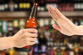 Hand reject a bottle of beer in the bar — Стоковое фото