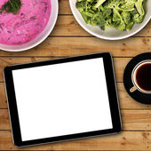 Digital tablet with white blank screen on dinner table — Stock Photo