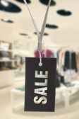 Sale sign hanging in clothes shop — Stock Photo