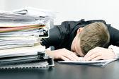 Yorgun ofis çalışanı ve bir yığın belgelerine — Stok fotoğraf