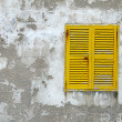 Closed yellow wooden window shutters on the old stone wall — Stock Photo