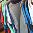 Colorful t-shirts on the hanger in the clothes shop — Stok fotoğraf