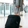 Woman's legs and travel suitcase at international airport — Stock Photo #26239789