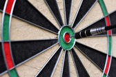 Dartboard with dart in the center — Stock Photo