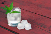 Glass of water with ice cubes and mint on old wooden table — Stock Photo