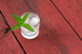 Glass of cold water with ice and mint on old wooden table — Stock Photo