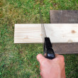 Sawing plank on a green grass background — Stock Photo