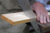 Wood workshop. carpenter cutting plank with hand saw — Stock Photo