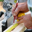 Carpenter take notes on a wooden board before cutting — Stock Photo #28972859