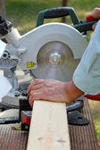 Carpenter cutting wooden plank with circular saw — Stock Photo