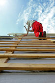 Construction worker with a hammer on the roof — Stock Photo