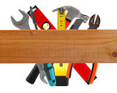 Different construction tools and wooden plank — Stock Photo