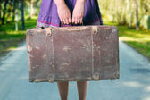 Girl with luggage on the road — Stock Photo