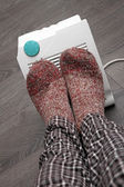 Feet with wool socks and electric heater — Stock Photo
