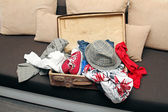 Opened suitcase full with clothes on couch — Stock Photo