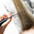 Woman cutting long hair with scissors — Stock Photo