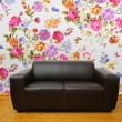 Interior with brown leather couch against colorful floral wall — Stock Photo