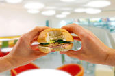 Hands hold a burger in fast food restaurant — Stock Photo