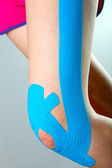 Physiotherapy - knee with blue kinesio tape — Stock Photo
