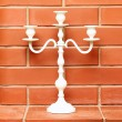 Stock Photo: White candlestick on brick background