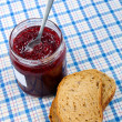 Stock Photo: Bread and jar with raspberry jam on blue tablecloth