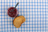 Jar with raspberry jam and sliced bread on blue tablecloth — Stock Photo
