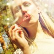 Young woman blowing soap bubbles outdoors — Stock Photo