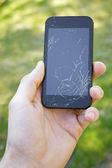 Smartphone with broken screen in the hand — Stock Photo