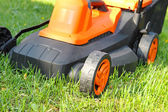Closeup of electric lawnmower on green grass — Stock Photo