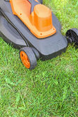 Electric lawnmower on green grass — Stock Photo