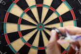 Hand throwing dart to dartboard — Stock Photo