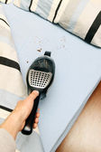 Cleaning crumbs out of bed with vacuum cleaner — Stock Photo