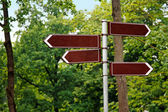 Blank way direction signs on green tree background — Stock Photo