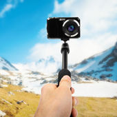 Taking selfie - hand hold monopod with photo camera — Stock Photo