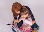Mother and daughter are reading a book — Stock Photo