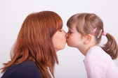 A young mother is kissing her daughter — Stock Photo