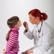 The pediatrician looks a little girl in the mouth — Stock Photo #20047883