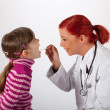 The pediatrician looks a little girl in the mouth — Stock Photo #20047913