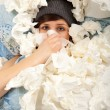 The young girl is lying sick in bed and blowing her nose — Stock Photo
