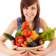 A young woman with a basket full of vegetables — Stock Photo #25111273