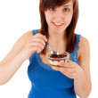 The young woman is eating dessert from a cup — Stock Photo