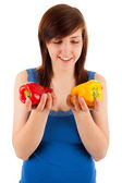The young woman has red and yellow pepper in her hands — Stock Photo